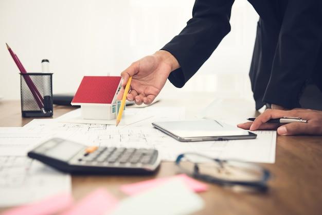 Agent nieruchomości dyskutuje pracę z projektami i modelem domu na stole