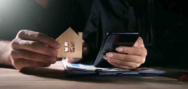 Agent nieruchomości i kierownik sprzedaży trzymający model domu za pomocą smartfona