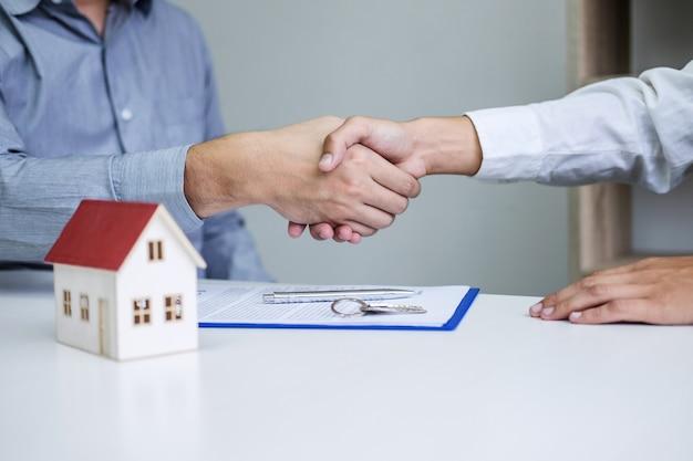 Agent nieruchomości i klienci, ściskając dłonie, świętując ukończony kontrakt
