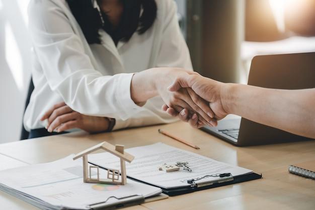 Agent nieruchomości i klient uścisk dłoni po zakończonej umowie o ubezpieczenie mieszkania i kredyt inwestycyjny.