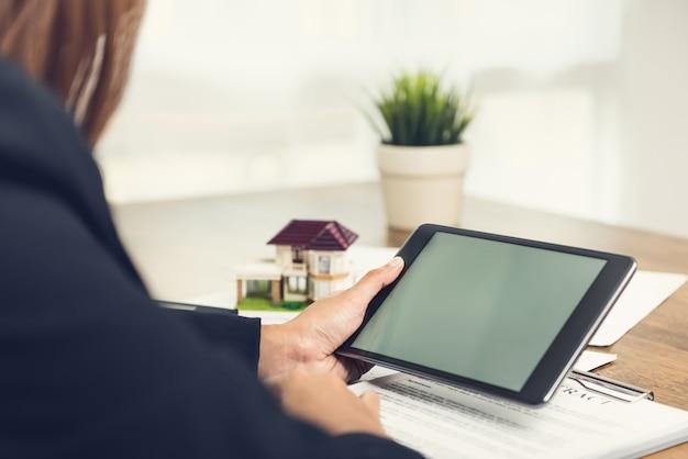 Agent nieruchomości lub architekt pracujący nad swoim projektem przy użyciu komputera typu tablet