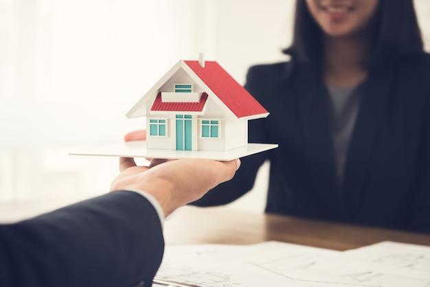Agent nieruchomości lub architekt przedstawiający model domu klientowi