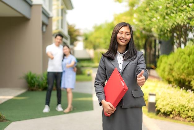 Agent nieruchomości lub pośrednik w handlu nieruchomościami kobieta uśmiecha się i trzyma czerwony plik z kciukiem do góry