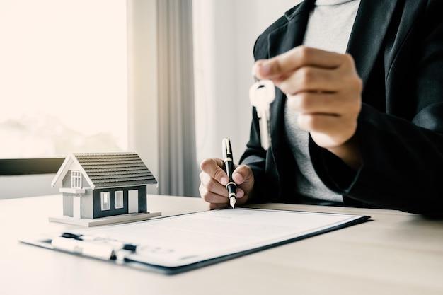 Agent nieruchomości podpisuje kluczem modelu domu i wyjaśnia kupującemu ubezpieczenie kontrahenta
