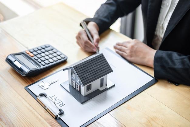 Agent nieruchomości podpisuje umowę dokument umowy na ubezpieczenie domu zatwierdzającą zakupy