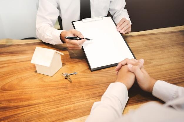 Agent nieruchomości pokazujący podpis kontraktu z klientem na zawarcie umowy wyceny