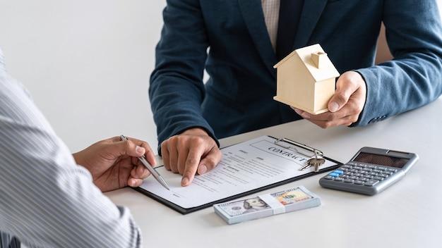 Agent nieruchomości prezentuje kredyt mieszkaniowy i wysyła klucze do klienta po podpisaniu umowy