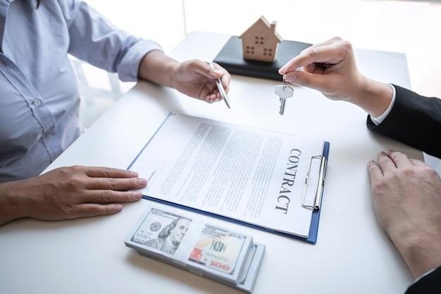 Agent nieruchomości przedstawia kredyt mieszkaniowy i wysyła klucze do klienta po podpisaniu umowy kupna domu z zatwierdzonym formularzem wniosku o nieruchomość, koncepcja ubezpieczenia domu.