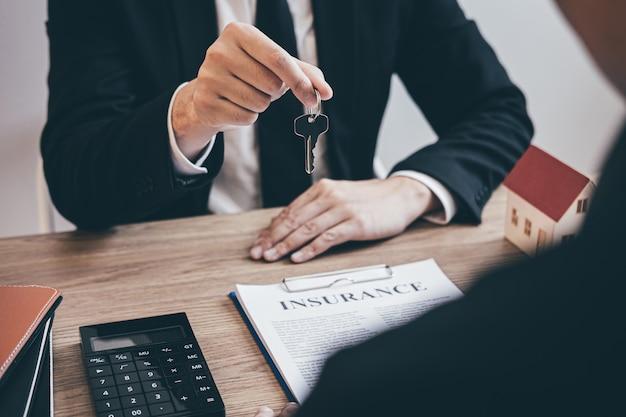 Agent nieruchomości przekazujący klientowi klucze do domu po podpisaniu umowy nieruchomości z zatwierdzonym wnioskiem o kredyt hipoteczny, dotyczący oferty kredytu hipotecznego i ubezpieczenia domu