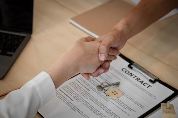 Agent nieruchomości ściska dłoń swojemu klientowi po podpisaniu umowy.