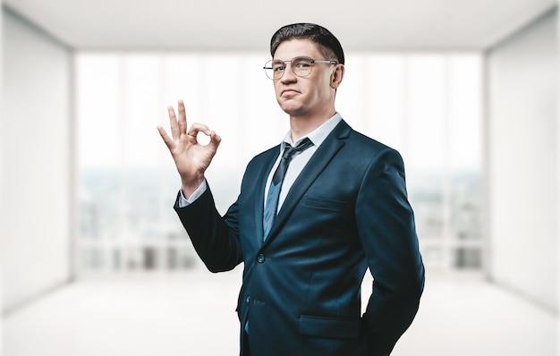 """Agent nieruchomości stoi w jasnym biurze i pokazuje aparatowi znak """"ok"""""""