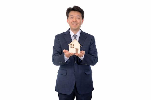 Agent nieruchomości trzyma dom z zabawkami