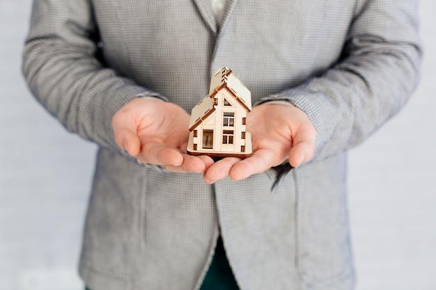 Agent nieruchomości trzyma drewnianą figurkę