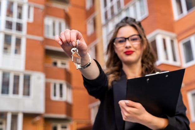 Agent nieruchomości trzyma klucz przed nowym domem jako tło. koncepcja sprzedaży