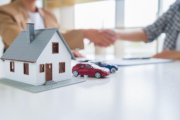Agent nieruchomości uścisk dłoni z klientem w celu zawarcia umowy kupna domu,