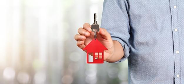 Agent nieruchomości w ręku przekazuje klucze do domu