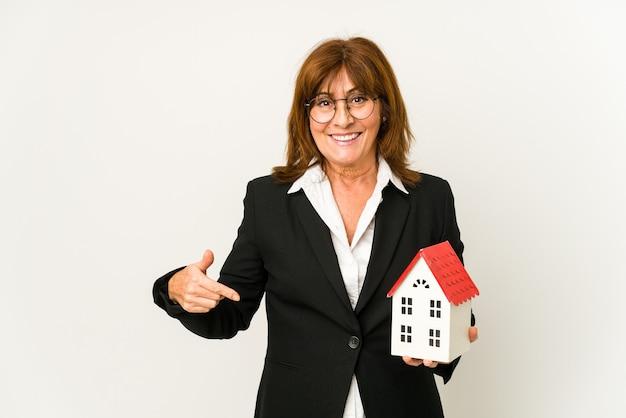 Agent nieruchomości w średnim wieku trzyma model domu na białym tle osoba, wskazując ręką na przestrzeni kopii koszuli, dumny i pewny siebie