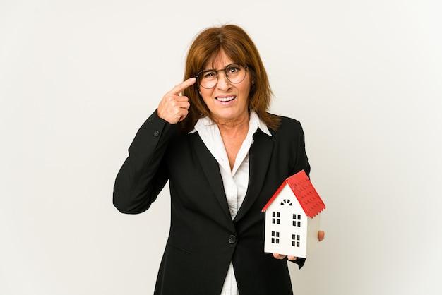 Agent nieruchomości w średnim wieku trzyma model domu na białym tle, pokazując gest rozczarowania palcem wskazującym.