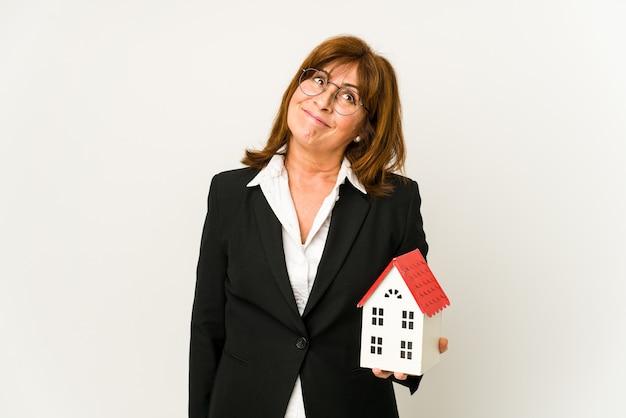 Agent nieruchomości w średnim wieku, trzymając model domu na białym tle, marzy o osiągnięciu celów i zamierzeń