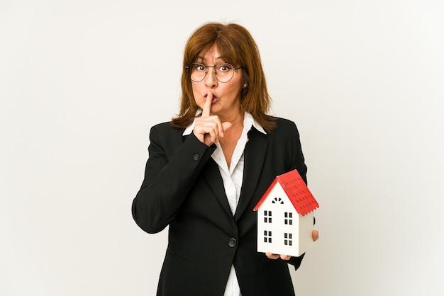 Agent nieruchomości w średnim wieku trzymający model domu na białym tle, trzymający w tajemnicy lub proszący o ciszę