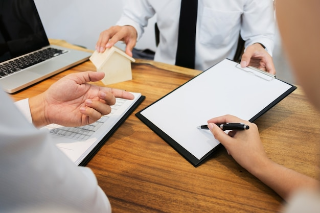 Agent nieruchomości z klientem podpisującym umowę i analizującą wycenę