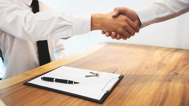 Agent nieruchomości z klientem podpisuje umowę i analizuje wycenę