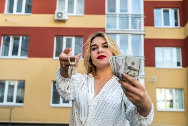 Agent nieruchomości z kluczem przed nowym domem. przeprowadzka do domu lub wynajem nieruchomości