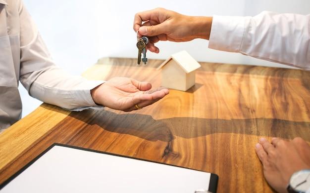 Agent nieruchomości z podpisaniem umowy z klientem podając klucz kupić / wynająć dom