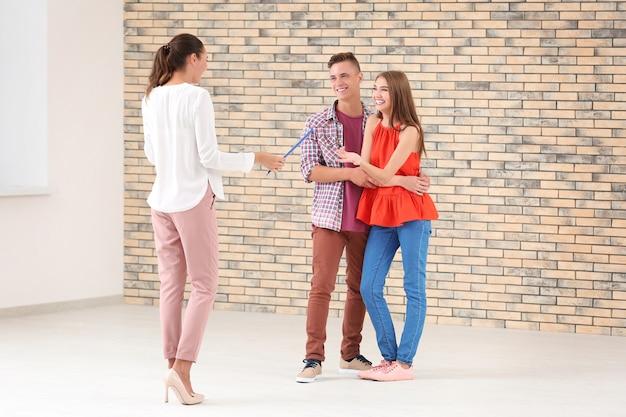 Agent nieruchomości ze schowkiem i szczęśliwa para w nowym mieszkaniu
