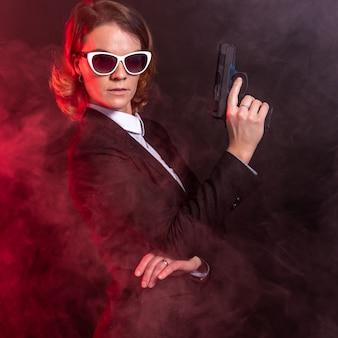 Agent ochrony z pistoletem w ręku i okularami przeciwsłonecznymi na oczach