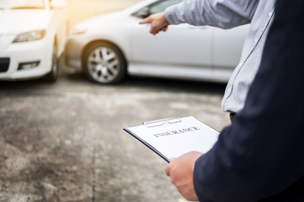 Agent piśmie w schowku podczas badania samochodu po wypadku