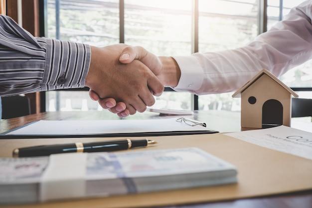 Agent pośrednika w obrocie nieruchomościami i klient ściskają ręce po podpisaniu dokumentów kontraktowych na zakup nieruchomości