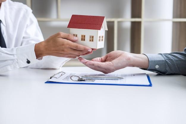 Agent pośrednika w obrocie nieruchomościami przedstawiający i konsultujący się z klientem w celu podjęcia decyzji podpisania formularza umowy ubezpieczenia, model domowy