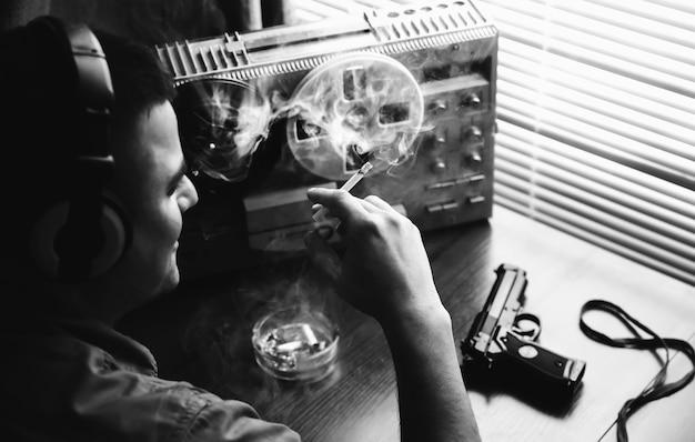 Agent specjalny podsłuchuje na magnetofonie szpulowym. oficer pali papierosa. kgb szpieguje rozmowy. pistolet na stole.