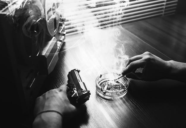 Agent specjalny podsłuchuje na magnetofonie szpulowym. oficer pali papierosa. kgb szpieguje rozmowy. ręka z papierosem w pobliżu popielniczki. pistolet na stole.