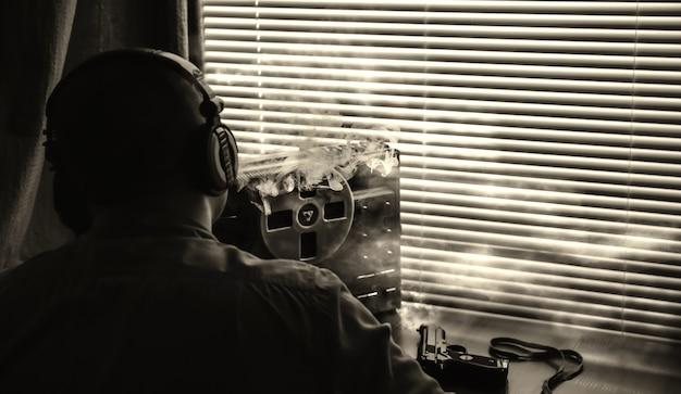 Agent specjalny podsłuchuje na magnetofonie szpulowym. oficer pali papierosa. kgb szpieguje rozmowy. zdjęcie sylwetki.