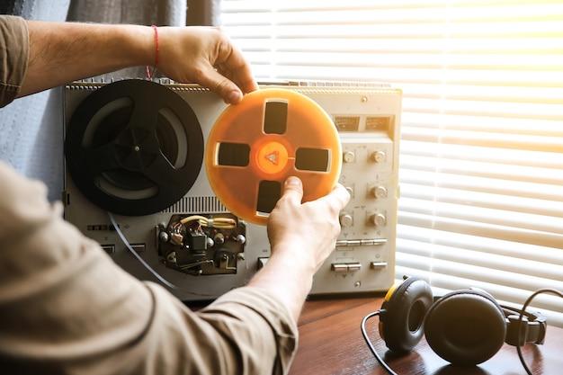 Agent specjalny zmienia film na magnetofonie szpulowym. kgb szpieguje rozmowy.