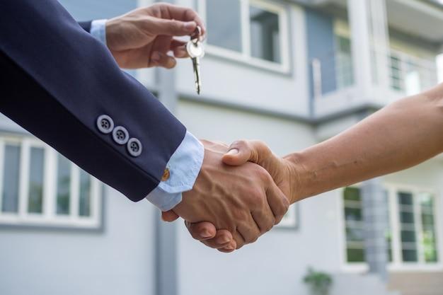 Agent sprzedaje uścisk dłoni domu kupującemu i przesyła klucz do domu kupującemu