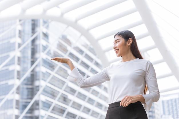 Agent sprzedaży biznesowej pracownik szczęśliwy uśmiech ręka obecny pokaż gest wyświetlania do sprzedaży produktów montaż na zewnątrz dla osoby reklamującej.