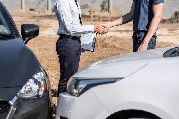 Agent ubezpieczeniowy i klient ściskają ręce po uzgodnieniu w sprawie roszczenia ubezpieczeniowego, oceniają badanie wypadku samochodowego, sprawdzanie i podpisywanie formularza zgłoszenia roszczenia po kolizji wypadku