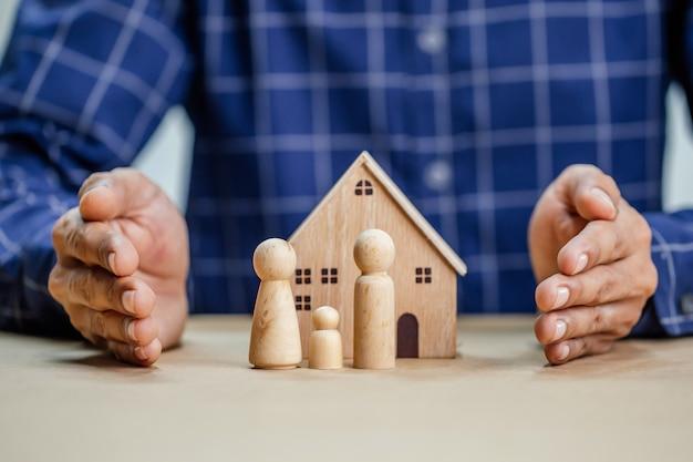 Agent ubezpieczeniowy kompletny drewniany model domu z ostatnim kawałkiem z ubezpieczeniem tekstu. koncepcja ochrony ubezpieczenia nieruchomości (dom jednorodzinny).