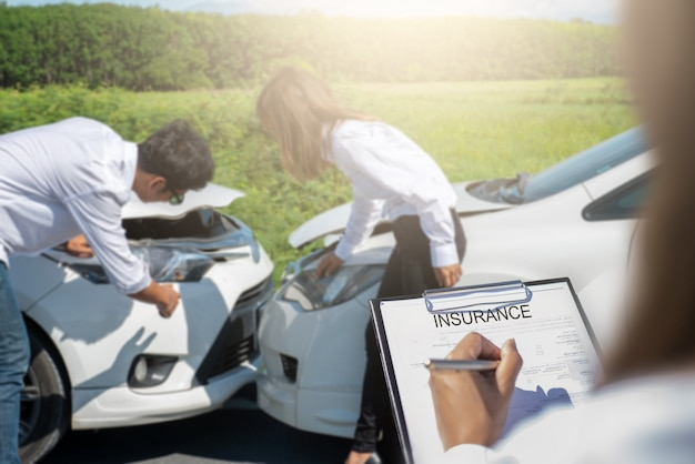 Agent ubezpieczeniowy piszący w schowku po samochodach powypadkowych.