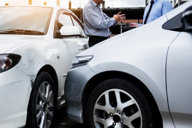 Agent ubezpieczeniowy pisze na schowku podczas gdy badający samochód po tym jak roszczenia roszczenia ocenia