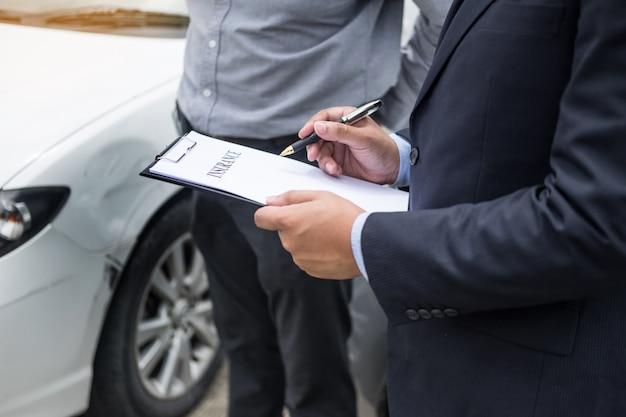 Agent ubezpieczeniowy pisze na schowku podczas gdy egzamininujący samochód po wypadku