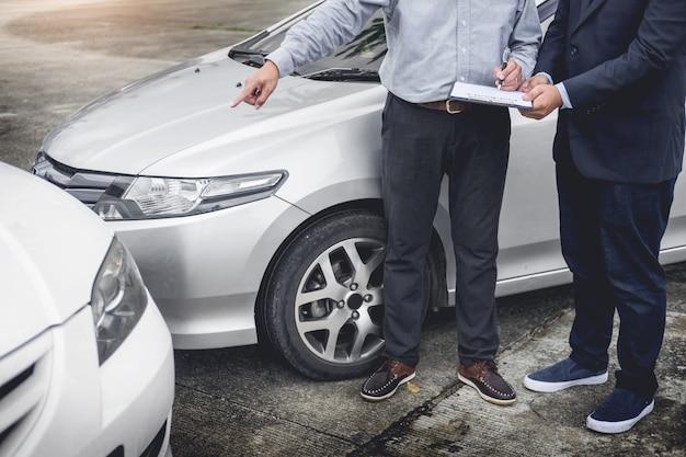 Agent ubezpieczeniowy pisze w schowku podczas gdy badający samochód po wypadkowego żądania