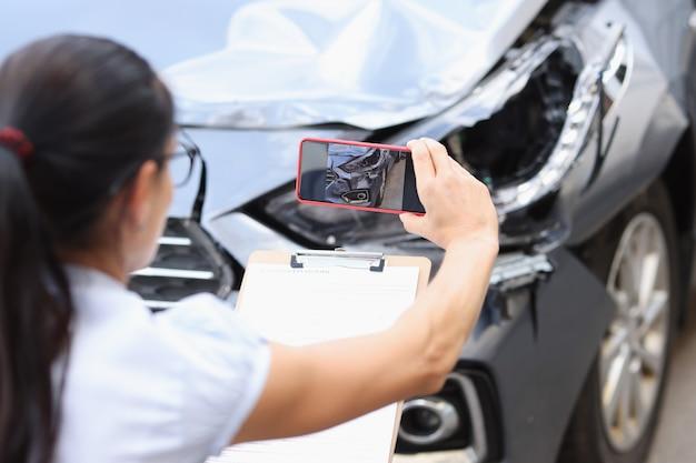 Agent ubezpieczeniowy robi zdjęcia uszkodzenia samochodu po wypadku na smartfonie wypełniając