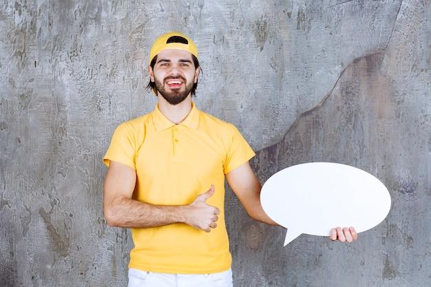 Agent usług w żółtym mundurze trzymający owalną tablicę informacyjną i pokazujący pozytywny znak ręki