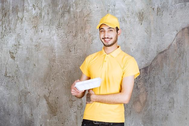 Agent usługi mężczyzna w żółtym mundurze, trzymając białe pudełko na wynos.