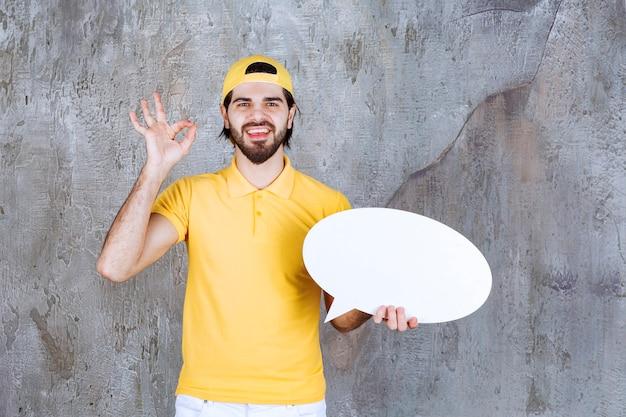 Agent usługi w żółtym mundurze, trzymając owalną tablicę informacyjną i pokazując pozytywny znak ręki.
