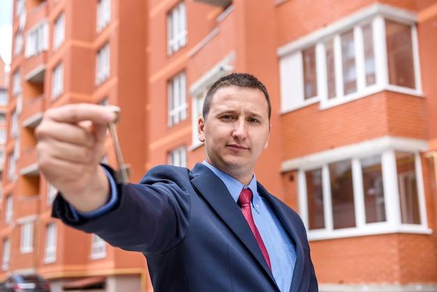 Agent w garniturze pokazujący klucz w pobliżu nowego budynku